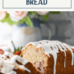 Side shot of sliced loaf of strawberry quick bread with text title box at top