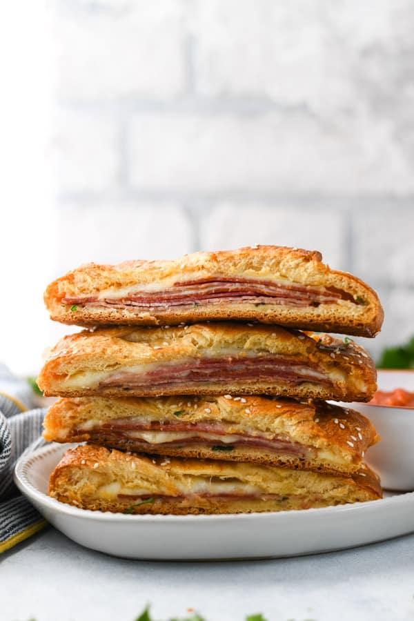Stack of stromboli sandwiches on a white platter