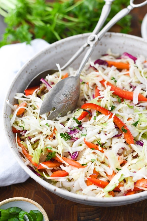 Close up side shot of a big bowl full of vinegar based coleslaw with serving tongs