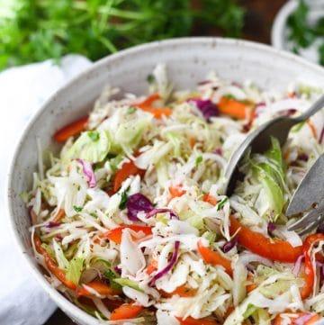 Close up side shot of a bowl of vinegar coleslaw