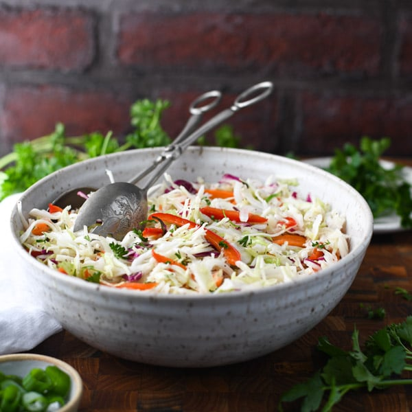 Square image of a white bowl full of oil and vinegar coleslaw in front of a brick wall