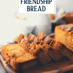 Sliced loaf of Amish friendship bread on a wooden cutting board with text title overlay