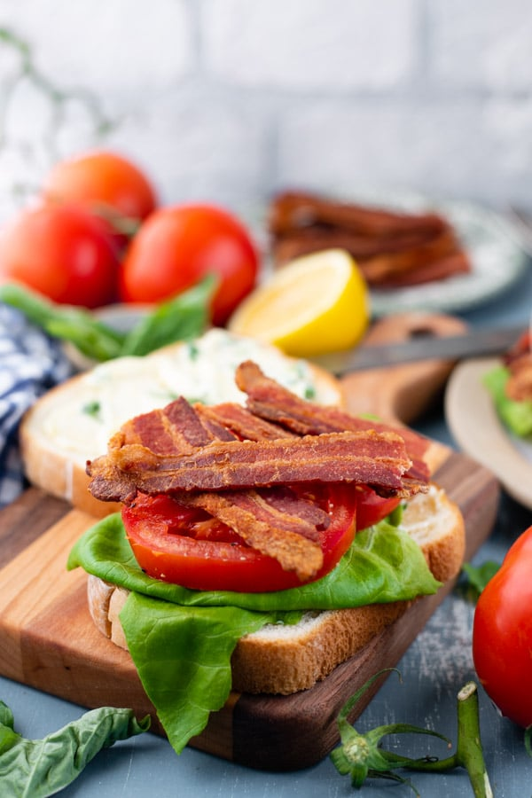 Side shot of a deluxe BLT sandwich on a wooden cutting board