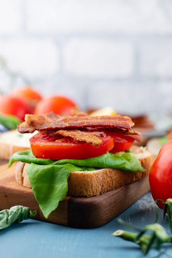 Side shot of a fancy BLT sandwich recipe with basil mayo