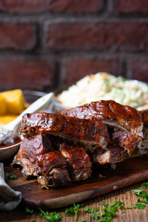 Side shot of baked baby back ribs on a cutting board in front of a brick wall
