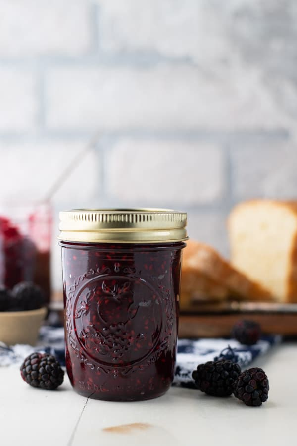 A jar of blackberry jam without pectin on a white table