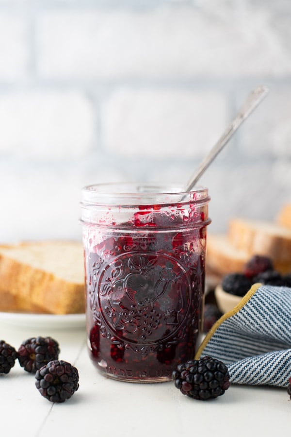 Front shot of a spoon in a mason jar full of old fashioned blackberry jam