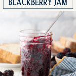 Spoon in a jar of old fashioned blackberry jam with text title box at top