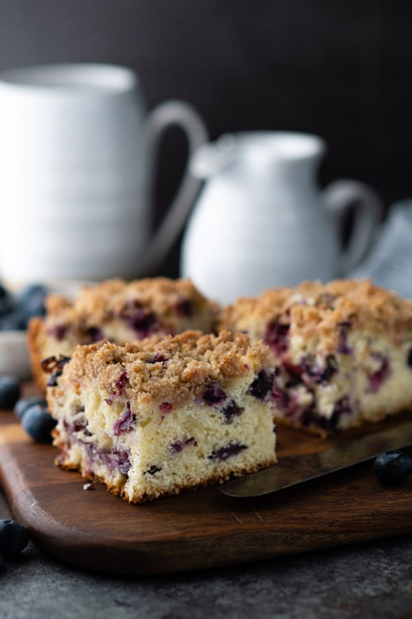 Slices of old fashioned blueberry buckle on a wooden cutting board