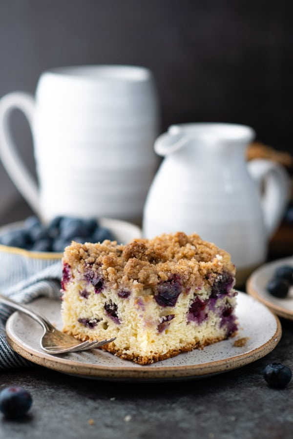 Side shot of a slice of blueberry buckle cake with cinnamon streusel topping