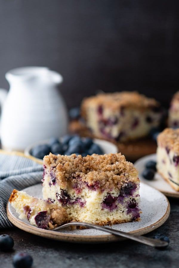 Side shot of a slice of blueberry buckle with a bite taken out of it
