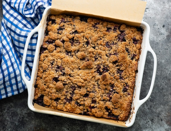 Overhead shot of moist blueberry buckle in a white baking dish