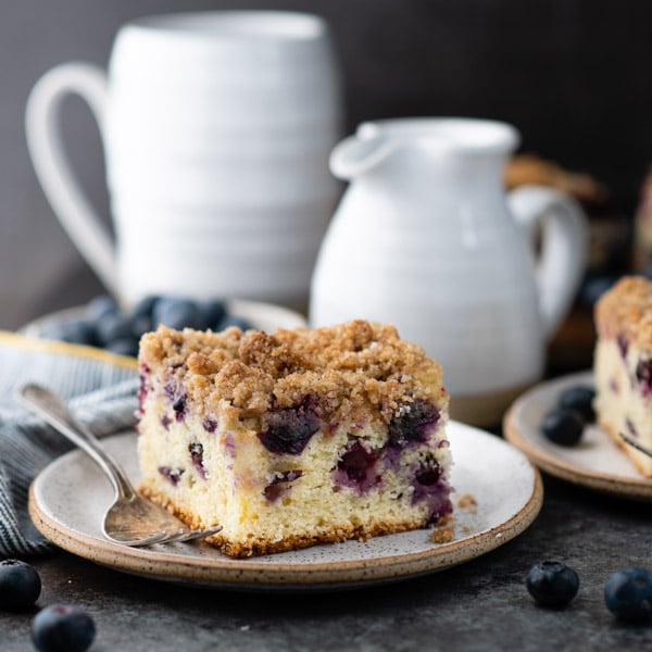 Square shot of classic blueberry buckle cake on a white plate