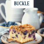 Slice of blueberry buckle coffee cake on a white plate with text title overlay