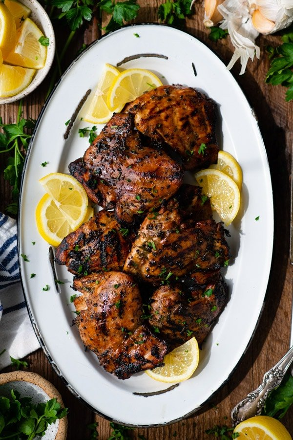 Overhead image of a platter of grilled chicken thighs marinade on a wooden table
