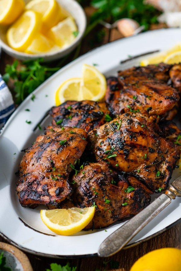 Side shot of a platter of chicken thighs with chicken thigh marinade from the grill