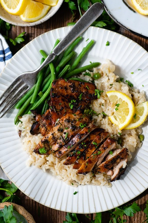 Overhead shot of marinated chicken thighs with rice and green beans.