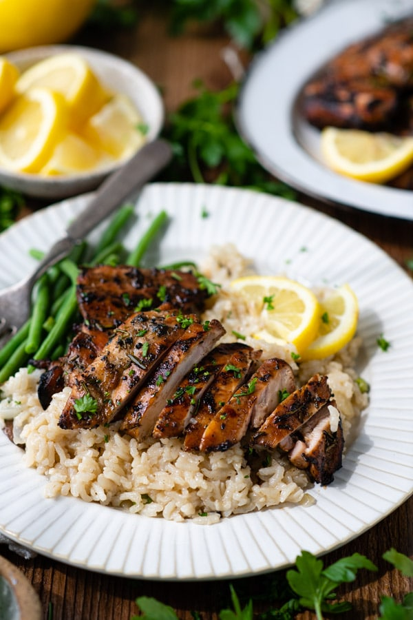Side shot of a plate of grilled chicken thighs with rice and green beans.