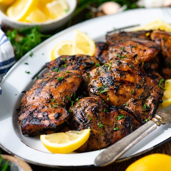 Grilled boneless skinless chicken thighs on a white platter