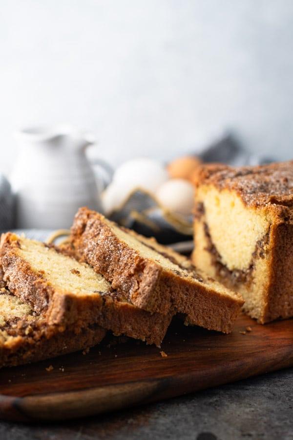 Loaf of cinnamon swirl bread sliced on a wooden cutting board
