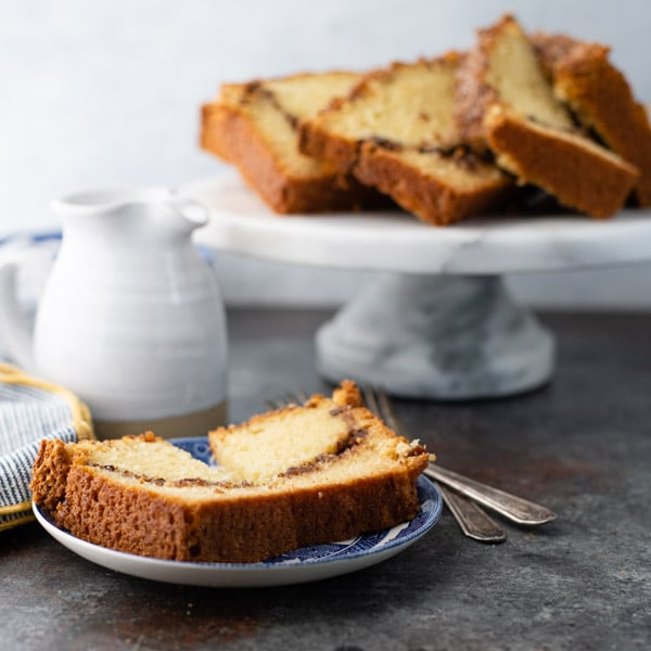 Square image of a piece of cinnamon swirl bread on a plate with cake stand and creamer in the background