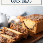 Front shot of cinnamon swirl bread on a cutting board with text title box at top