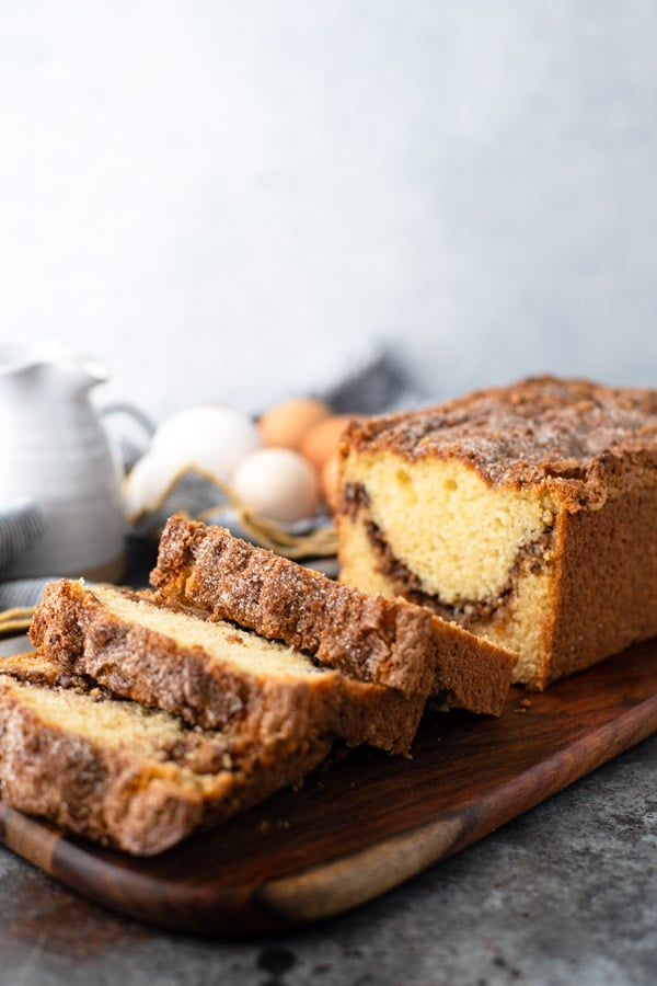 Side shot of a loaf of cinnamon bread on a wooden cutting board with eggs and cream in the background