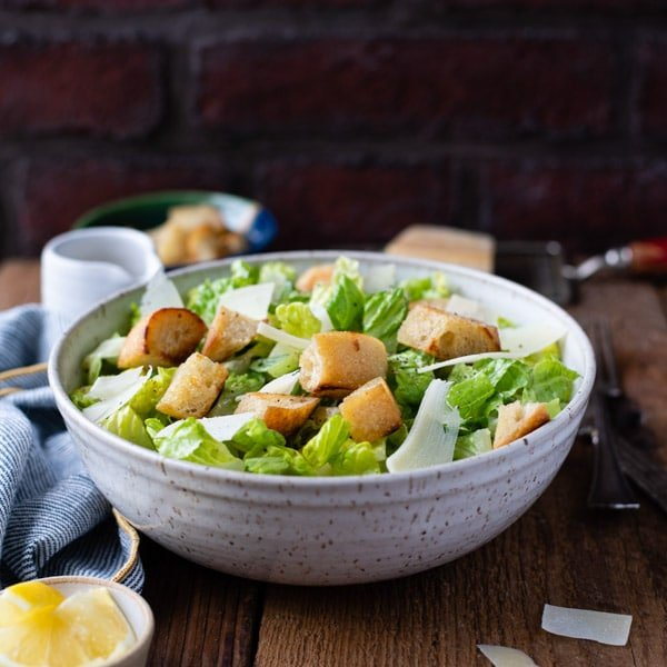 Square image of a side shot of a bowl of classic Caesar salad