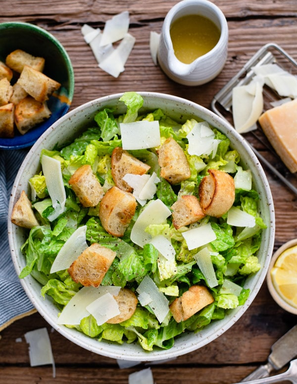 Overhead shot of easy Caesar salad recipe served in a bowl on a wooden table