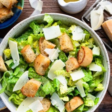 Homemade caesar salad served in a bowl on a wooden table
