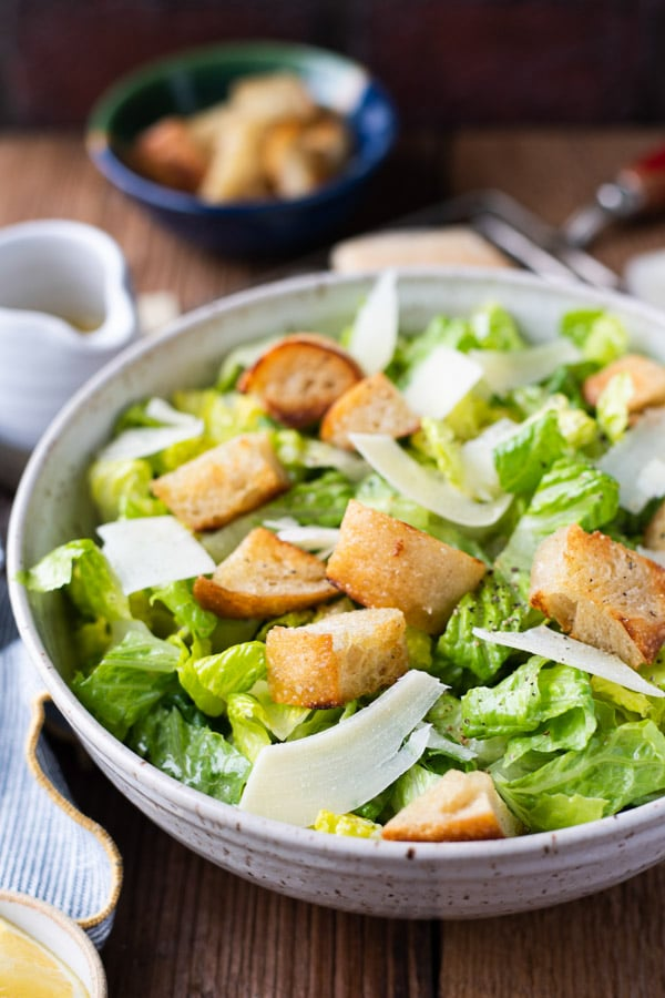 Side shot of a bowl of classic Caesar salad with homemade dressing and croutons