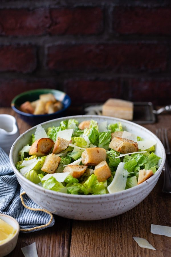Side shot of a classic caesar salad in a bowl in front of a black background