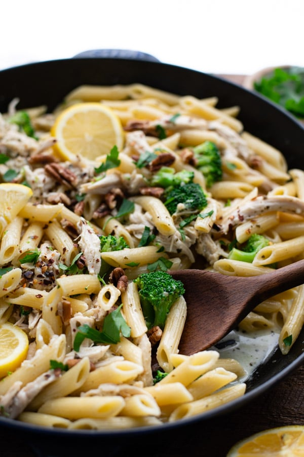 Close up side shot of a wooden spoon in a skillet of creamy chicken pesto pasta