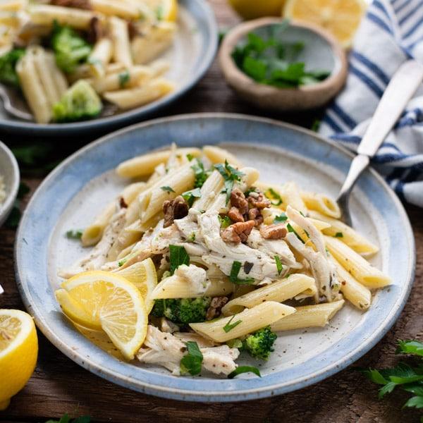 Square image of a plate of creamy chicken pesto pasta