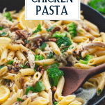 Wooden spoon stirring easy creamy pesto chicken pasta with text title overlay
