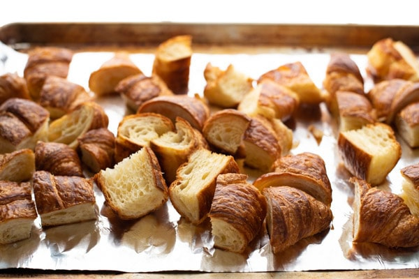 Chopped toasted croissants on a baking sheet