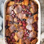 Overhead shot of a sweet croissant breakfast casserole with berries in a blue and white baking dish