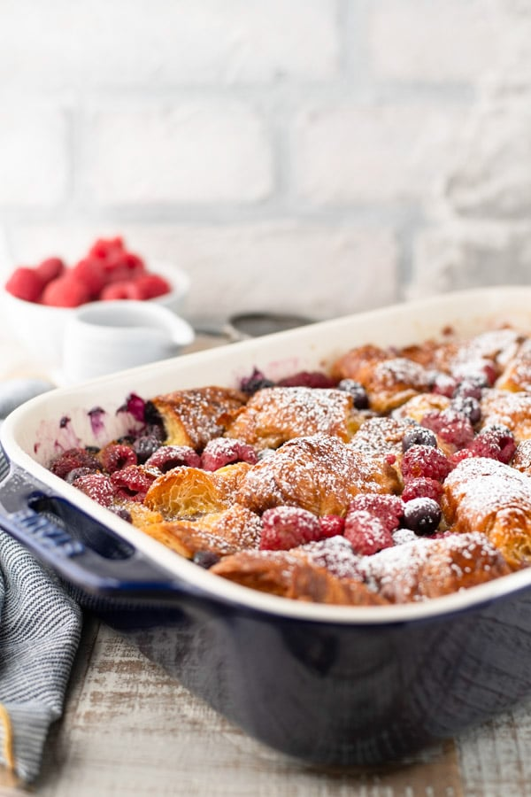 Side shot of a sweet croissant french toast casserole in a blue baking dish with fresh berries