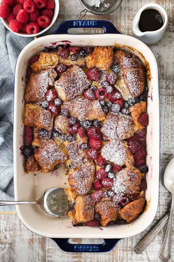 Overhead shot of sweet croissant breakfast casserole in a dish with a serving spatula