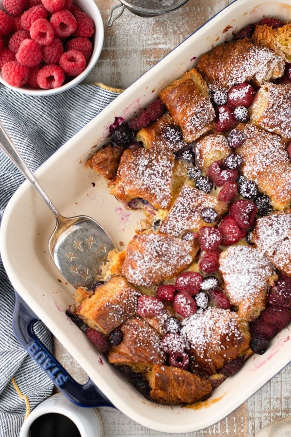 Overhead shot of a make ahead croissant breakfast casserole in a baking dish with fresh berries