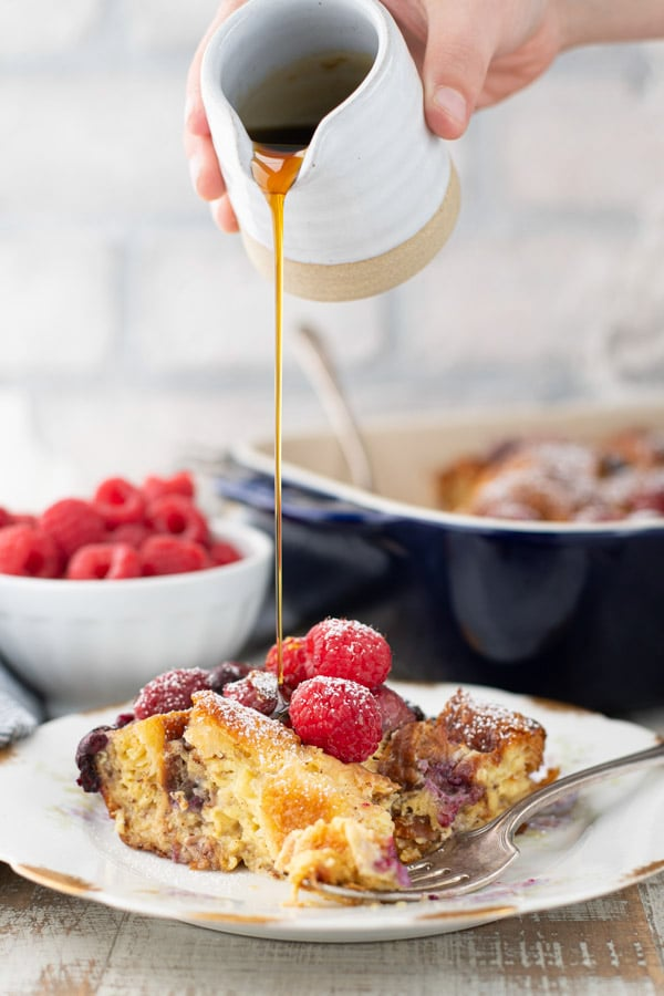 Pouring maple syrup on a sweet croissant breakfast casserole