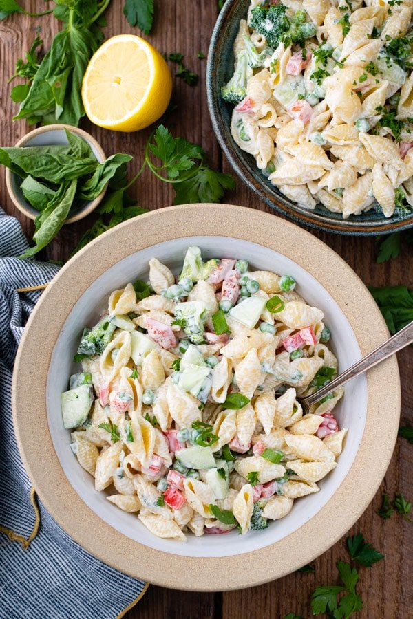 Overhead image of two bowls of easy pasta salad with mayo on a picnic table