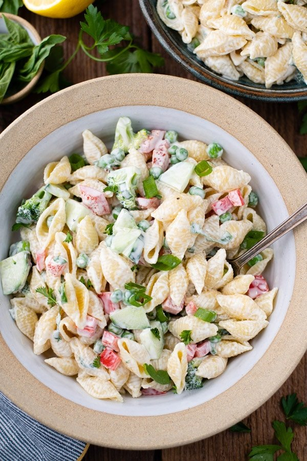 Close overhead shot of a bowl of creamy pasta salad on a wooden table