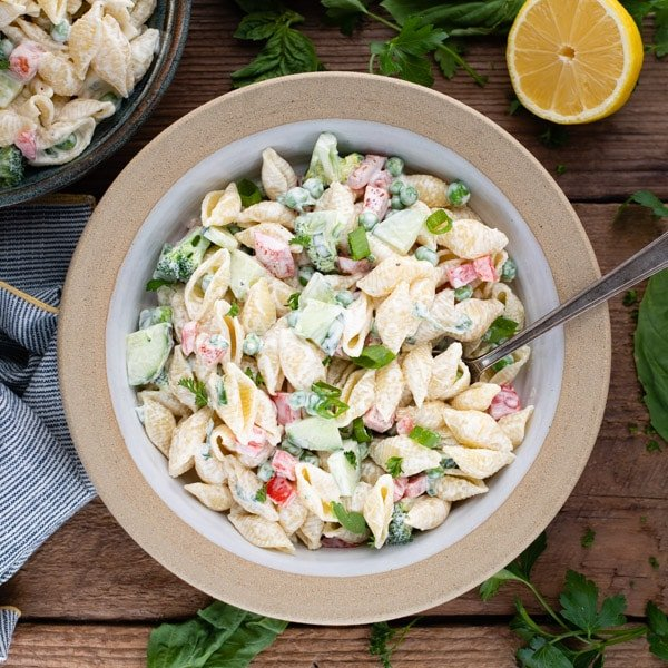 Square overhead shot of pasta salad with mayo in a white stoneware bowl