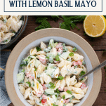 Overhead image of creamy pasta salad in a white stoneware bowl with text title box at top