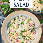Creamy pasta salad in a white stoneware bowl with text title overlay