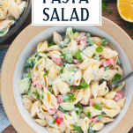 Close overhead shot of a bowl of creamy pasta salad with text title overlay