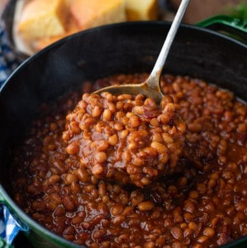 Close up shot of a ladle of homemade baked beans with bacon and molasses