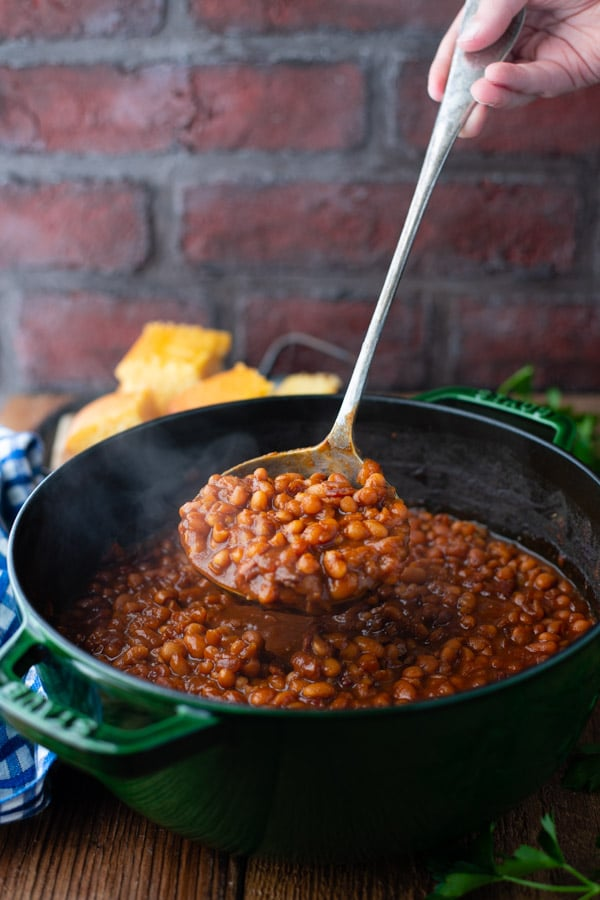 Hand holding a ladle full of homemade baked beans with bacon