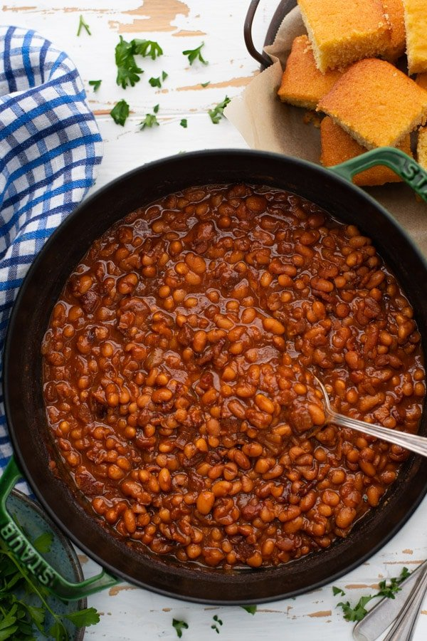Overhead image of Boston baked beans in a Dutch oven with a serving spoon